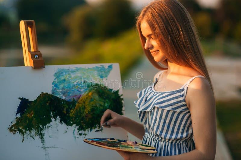 La bella ragazza disegna un'immagine nel parco facendo uso di una tavolozza con le pitture e una spatola Cavalletto e tela con un immagini stock