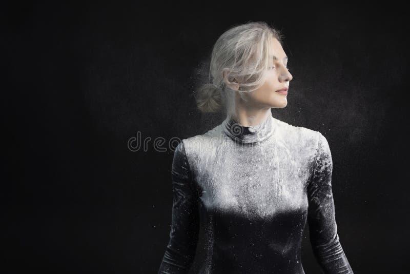 La bella ragazza esile che indossa una tuta relativa alla ginnastica nera coperta di polvere bianca del talco della polvere salta immagini stock