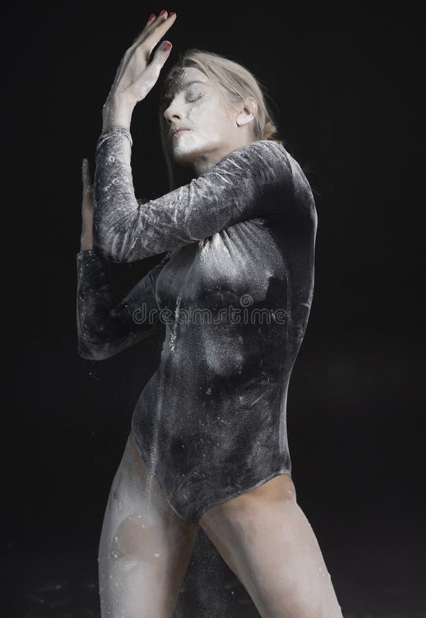 La bella ragazza esile che indossa una tuta relativa alla ginnastica nera coperta di polvere bianca del talco della polvere salta fotografia stock