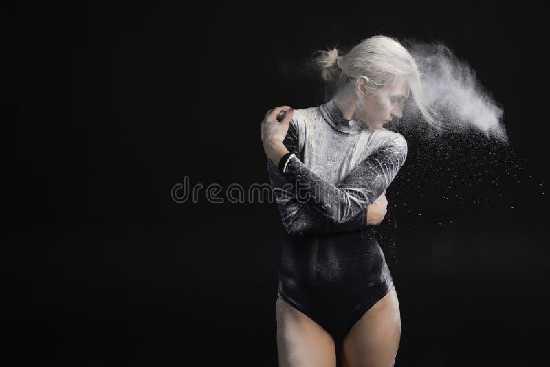 La bella ragazza esile che indossa una tuta relativa alla ginnastica nera coperta di polvere bianca si abbraccia e la polvere vol immagini stock