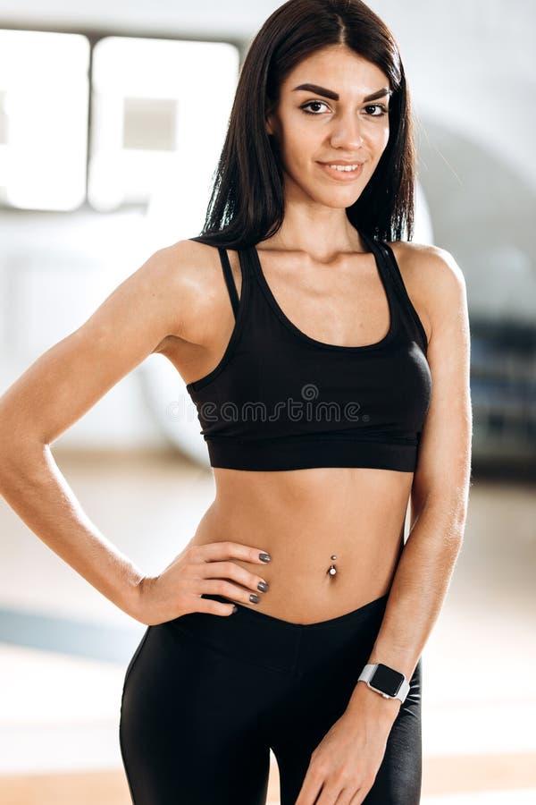 La bella ragazza esile vestita in abiti sportivi neri sta stando nella palestra nella stanza di forma fisica accanto allo specchi immagine stock libera da diritti