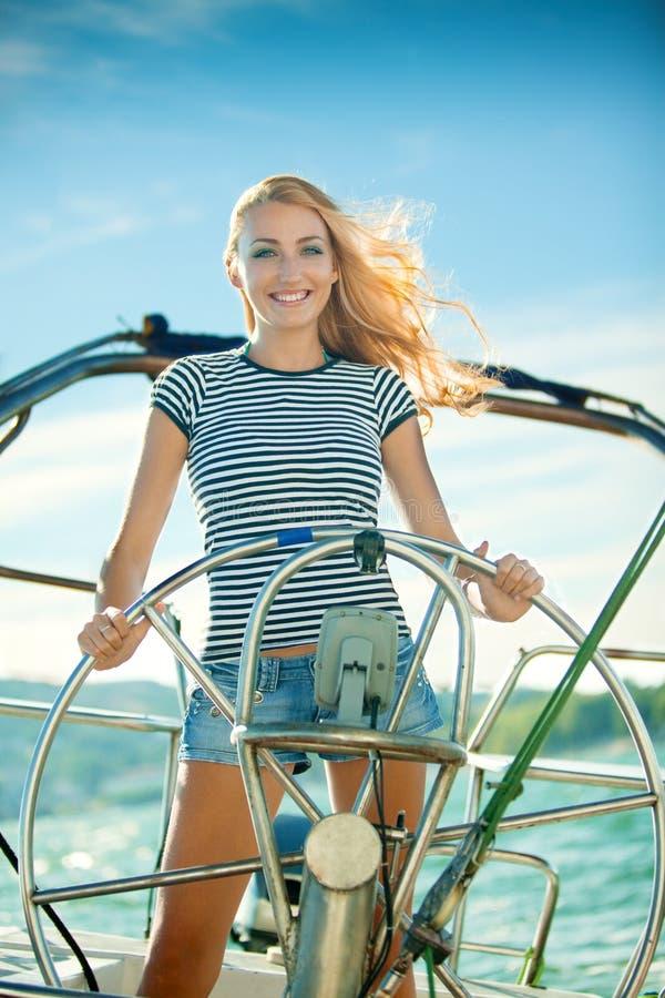 La bella ragazza fa funzionare l'yacht fotografie stock libere da diritti