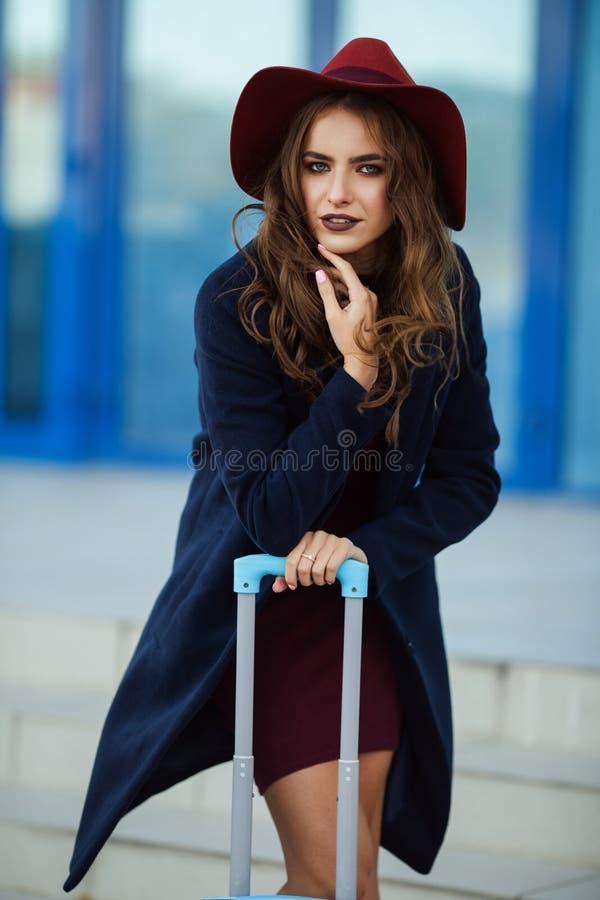 La bella ragazza felice sta portando i vestiti ed il cappello di modo vicino all'aeroporto con la valigia Foto di concetto del vi immagini stock
