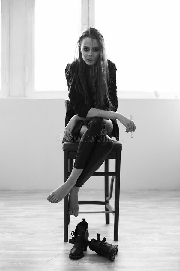 La bella ragazza fuma la seduta su una sedia immagine stock libera da diritti