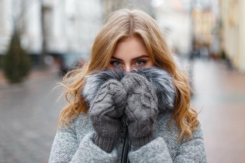 La bella ragazza in guanti tricottati nasconde il suo fronte fotografie stock libere da diritti