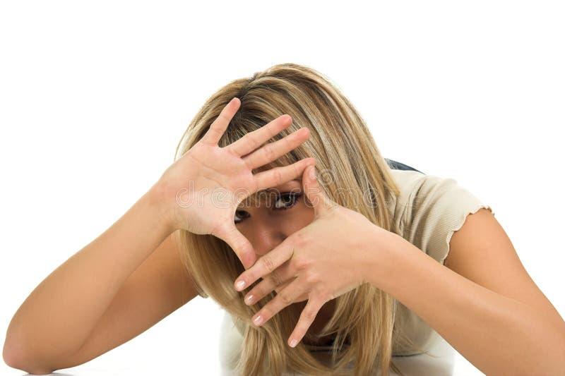 La bella ragazza ha incorniciato il suo fronte con le mani fotografia stock