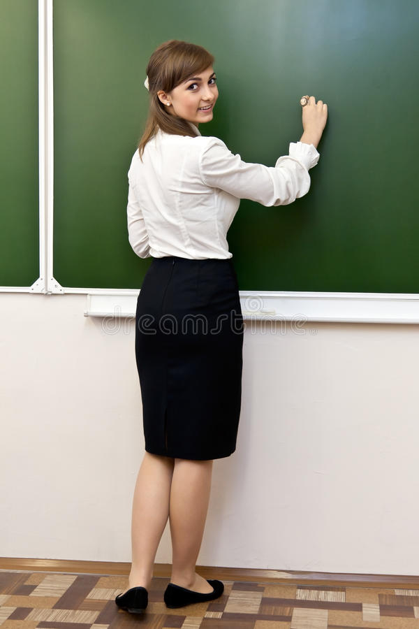 La bella ragazza ha scritto la lavagna fotografie stock