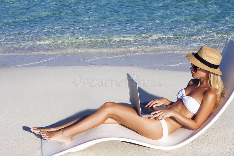 La bella ragazza ha una vacanza stagionale dell'inverno sulla spiaggia in paese esotico fotografia stock