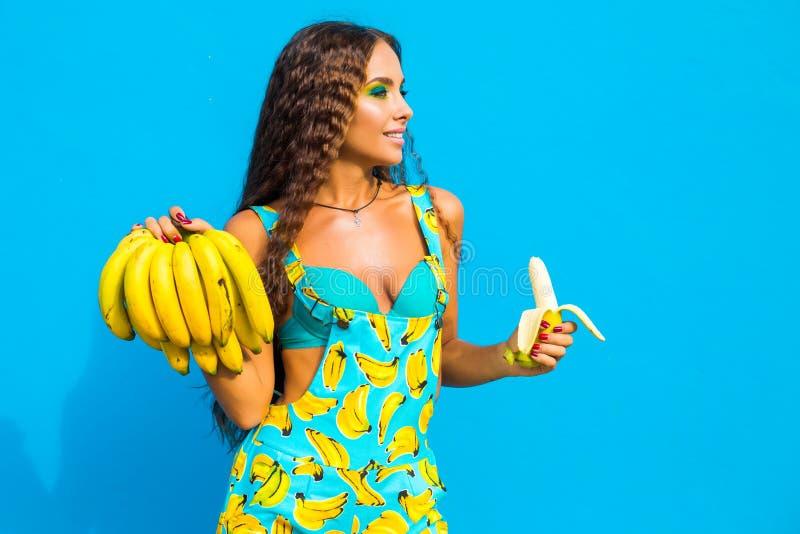 La bella ragazza intelligente sveglia su un fondo del turchese, risate, tiene un casco di banane e li mangia, sguardo divertente  immagine stock libera da diritti