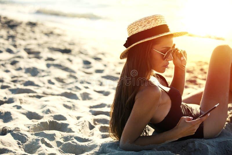 La bella ragazza invia un messaggio con il suo smartphone alla spiaggia fotografie stock libere da diritti