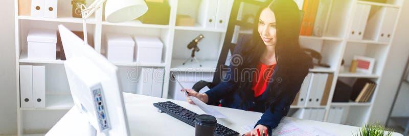 La bella ragazza lavora con i documenti, computer e calcolatore, sedentesi su una sedia nell'ufficio alla tavola fotografia stock