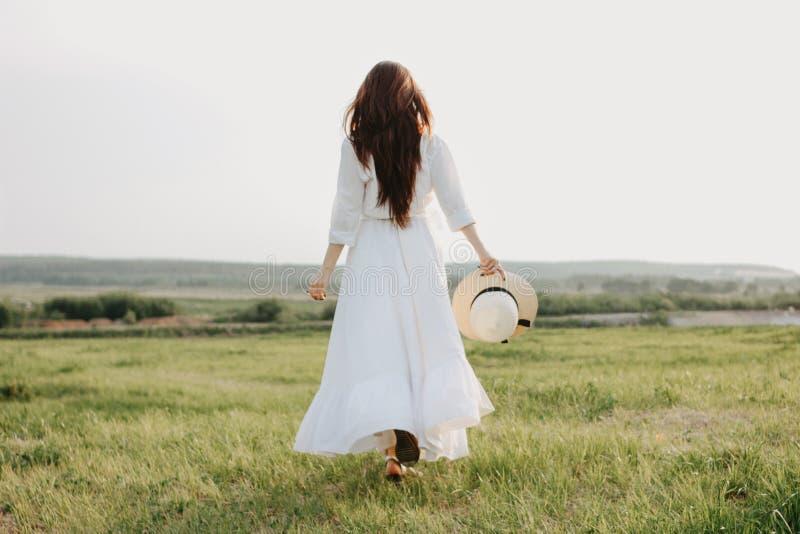 La bella ragazza lunga spensierata dei capelli in vestiti e cappello di paglia bianchi gode della vita nel giacimento della natur immagini stock libere da diritti