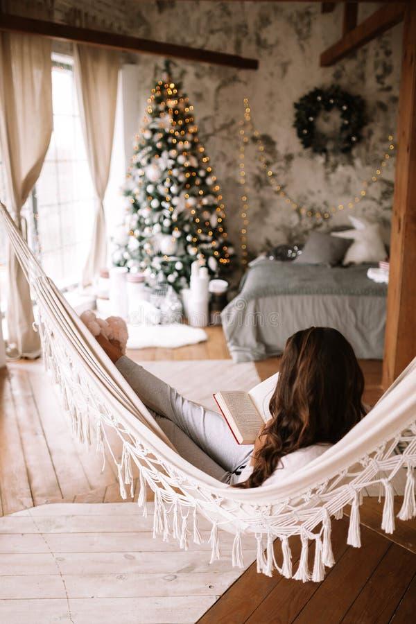 La bella ragazza mora vestita in pantaloni, maglione e pantofole calde legge un libro che si trova in un'amaca in un accogliente fotografia stock