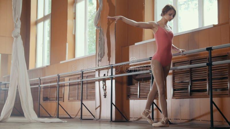La bella ragazza mostra la flessibilità stupefacente delle gambe della barra di balletto fotografia stock libera da diritti