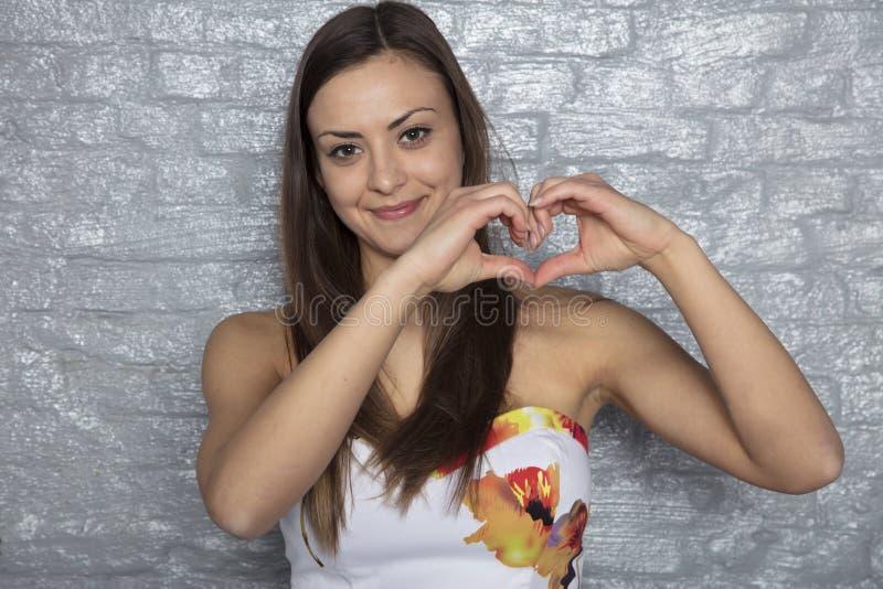 La bella ragazza mostra il cuore con la mano fotografie stock