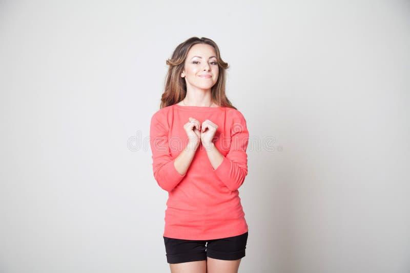 La bella ragazza mostra il cuore di simbolo delle mani fotografia stock
