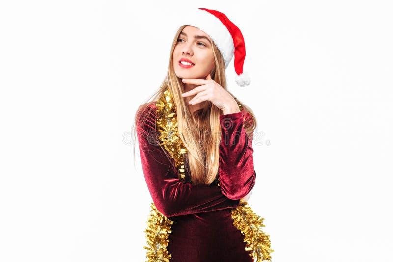 La bella ragazza nel cappello di Santa Claus distoglie lo sguardo meditatamente fotografia stock libera da diritti