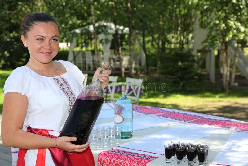 La bella ragazza nel costume ucraino nazionale presenta la bevanda alcolica nazionale fotografie stock