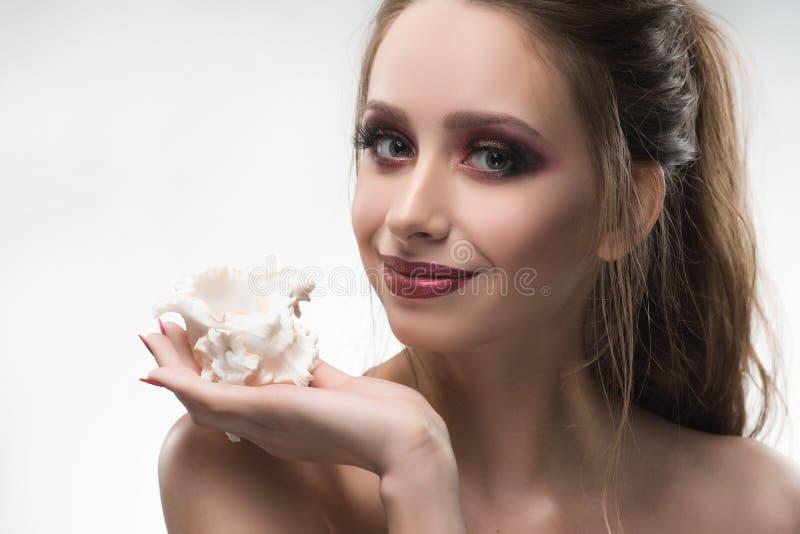 La bella ragazza nuda sorridente delle spalle tiene una conchiglia nella sua h immagini stock libere da diritti