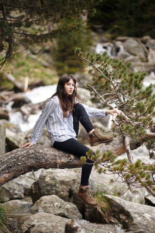La bella ragazza rimane sopra una montagna ed esamina l'orizzonte con un bello fondo Una foto variopinta della a fotografia stock