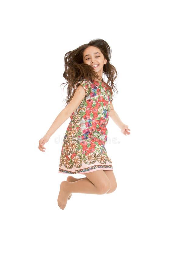 La bella ragazza salta le gambe attraversate fotografia stock