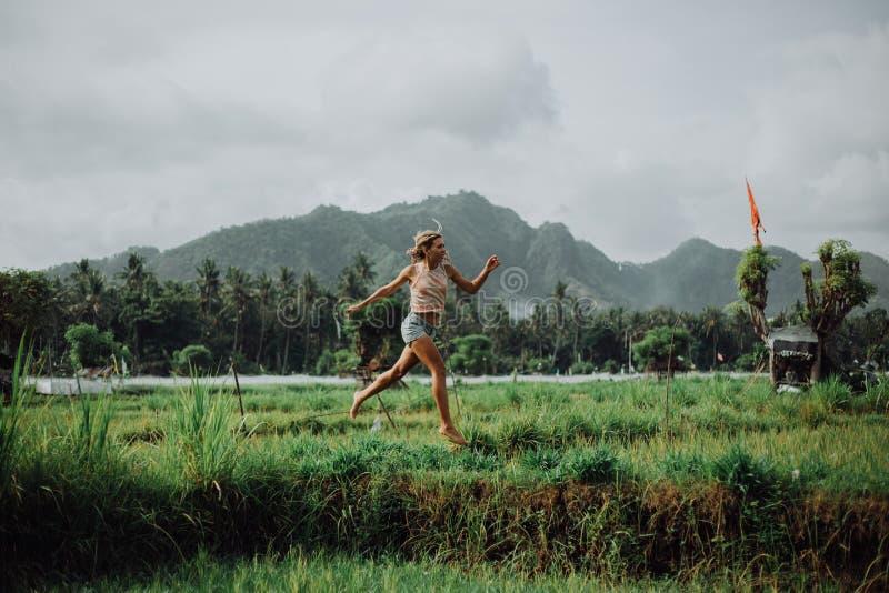La bella ragazza salta, le risaie incredibili, un vulcano nei precedenti e le montagne Priorità bassa fredda felice fotografia stock libera da diritti