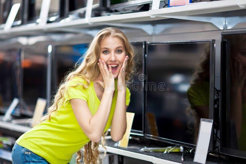 La bella ragazza sceglie un TV al plasma nel deposito immagini stock
