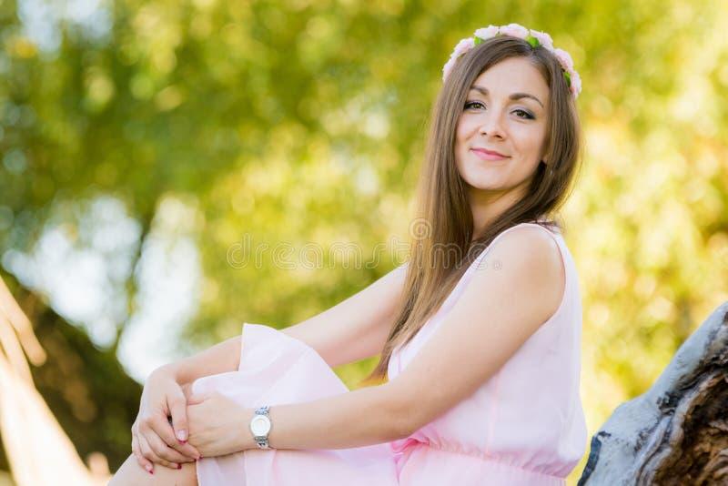 La bella ragazza si siede su un fondo illuminato dalle foglie del sole immagini stock libere da diritti