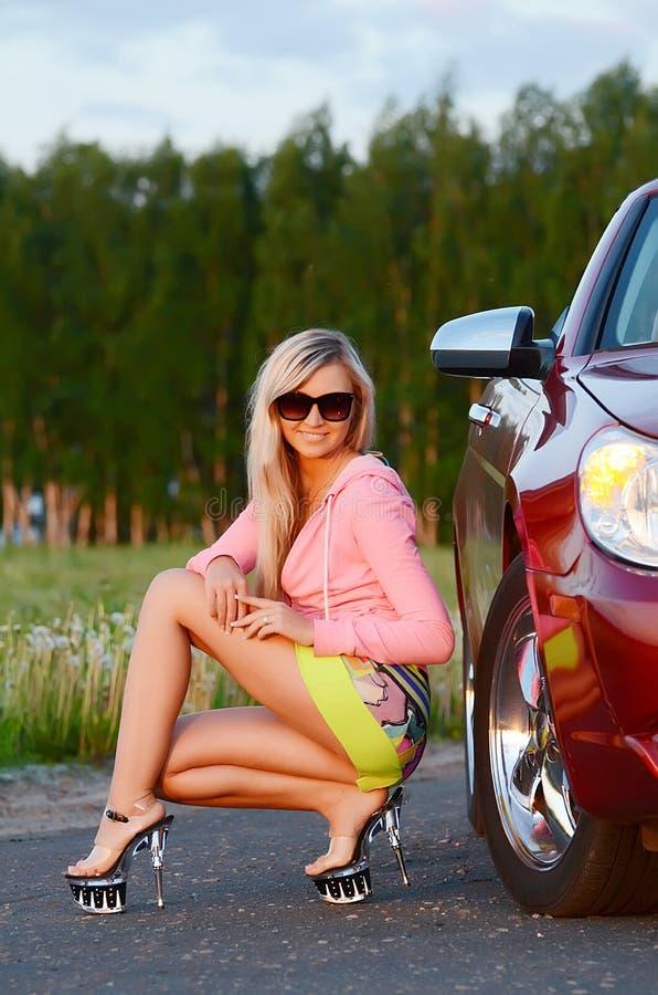 La bella ragazza si siede vicino all'automobile rossa fotografia stock