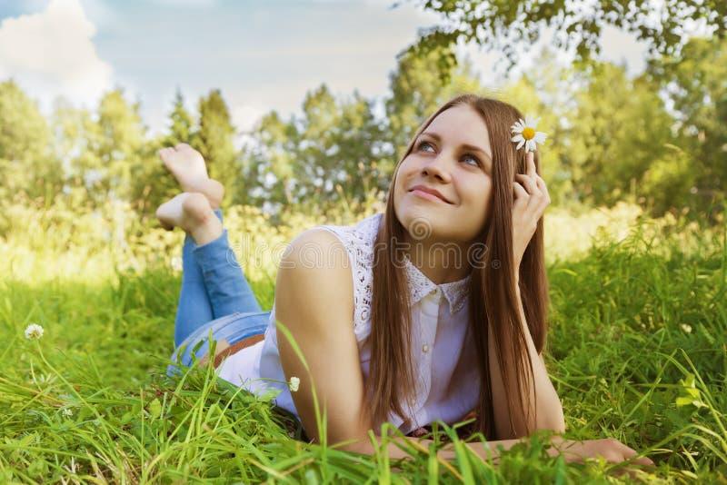 La bella ragazza si trova sul prato con i fiori della camomilla fotografie stock libere da diritti