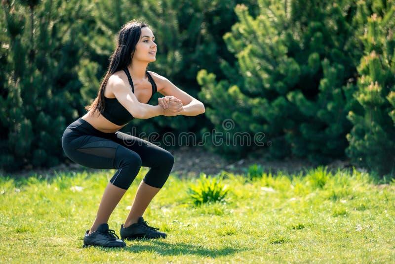 La bella ragazza snella con capelli scuri in un'uniforme di sport si accovaccia in natura, un simbolo degli stili di vita sani, f fotografia stock libera da diritti