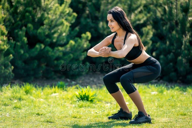 La bella ragazza snella con capelli scuri in un'uniforme di sport si accovaccia in natura, un simbolo degli stili di vita sani, f fotografie stock libere da diritti