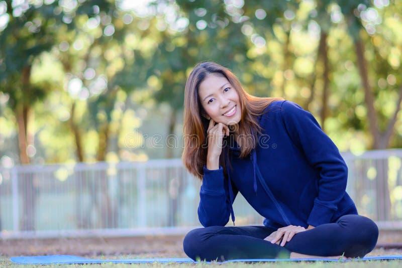 La bella ragazza sorridente con gli abiti sportivi è sedentesi e rilassantesi la i fotografia stock libera da diritti