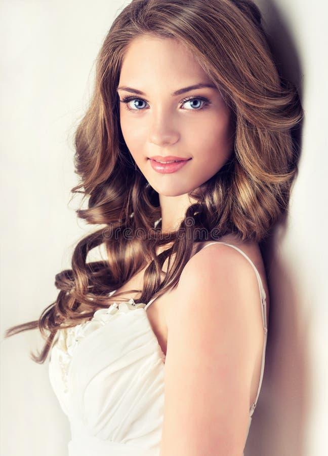 La bella ragazza sorridente, i capelli marroni con un'acconciatura elegante, capelli ondeggia, riccio immagini stock libere da diritti