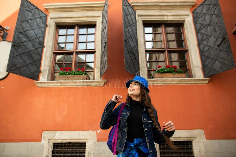 La bella ragazza sorridente in un cappello blu posa vicino alla vecchia casa rossa immagini stock libere da diritti
