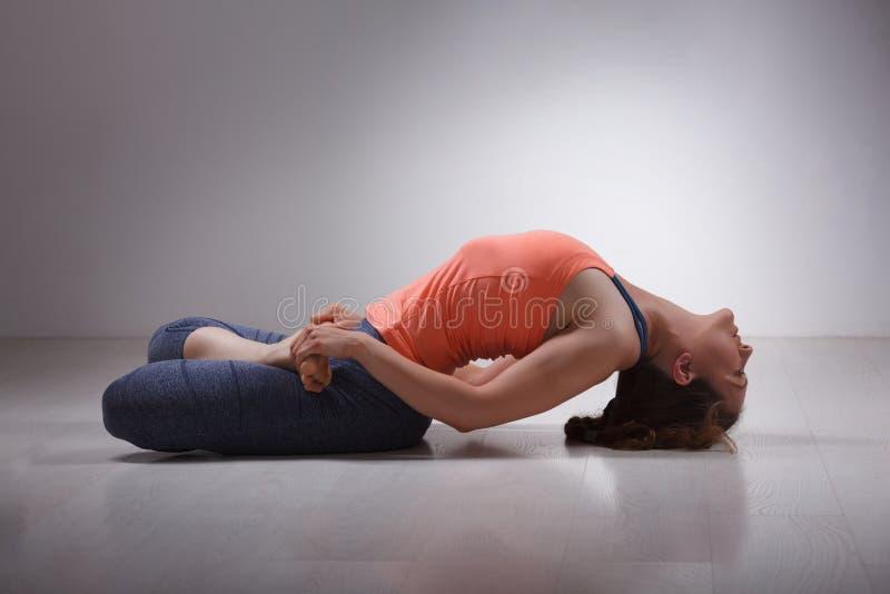 La bella ragazza sportiva degli Yogi di misura pratica l'yoga fotografia stock libera da diritti
