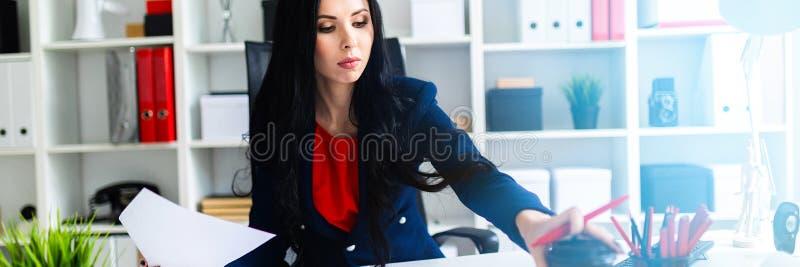 La bella ragazza sta lavorando con i documenti nell'ufficio alla tavola La ragazza sta ponendo un vetro sulla tavola con immagini stock libere da diritti