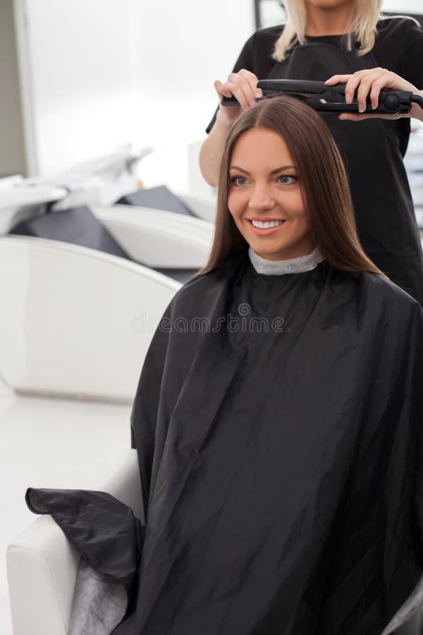 La bella ragazza sta ottenendo lei i capelli uguagliati fotografia stock