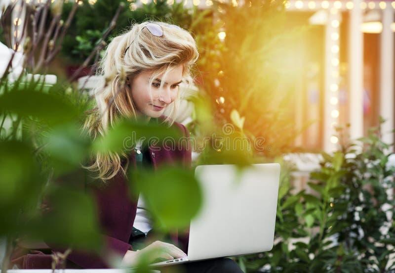 La bella ragazza sta sedendosi su un banco con un computer portatile in sue mani su una via fresca con la città Un lavoro di con fotografia stock libera da diritti