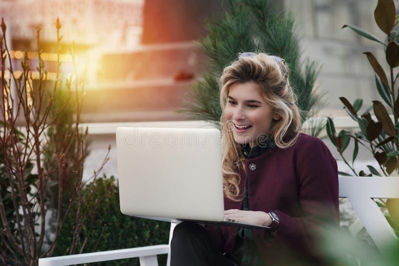 La bella ragazza sta sedendosi su un banco con un computer portatile in sue mani su una via fresca con la città Un lavoro di con fotografie stock