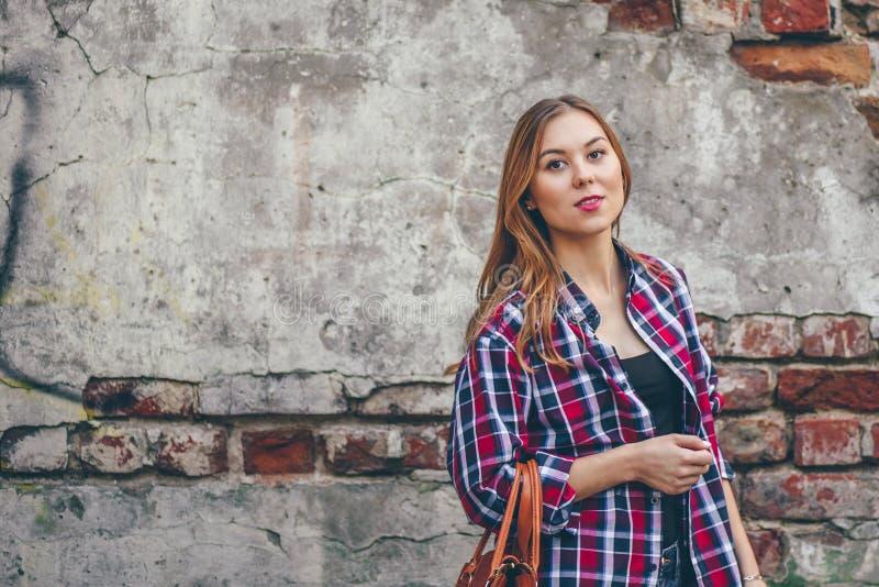 La bella ragazza sta stando contro il muro di mattoni fotografia stock libera da diritti