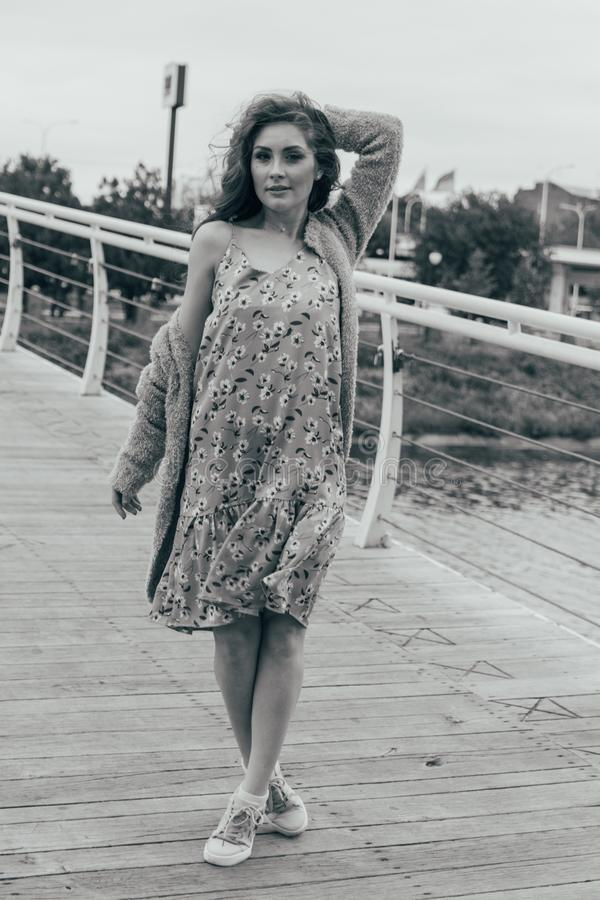 La bella ragazza sta sul ponte, il vento soffia nel suo fronte, sviluppante i suoi capelli Sorrisi della ragazza foto in bianco e fotografie stock