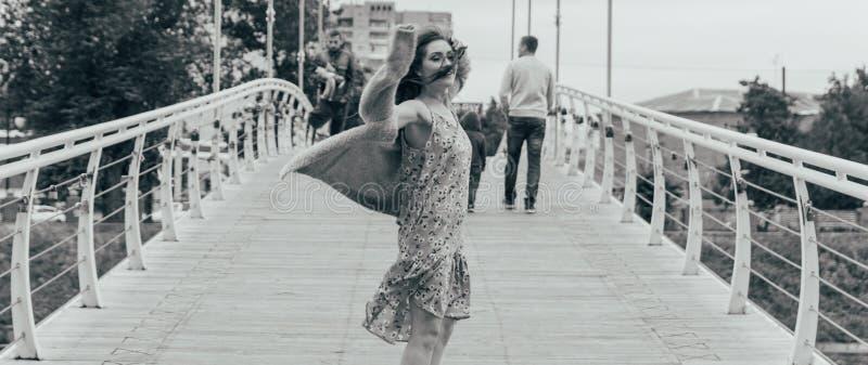 La bella ragazza sta sul ponte, il vento soffia nel suo fronte, sviluppante i suoi capelli Sorrisi della ragazza foto in bianco e immagine stock