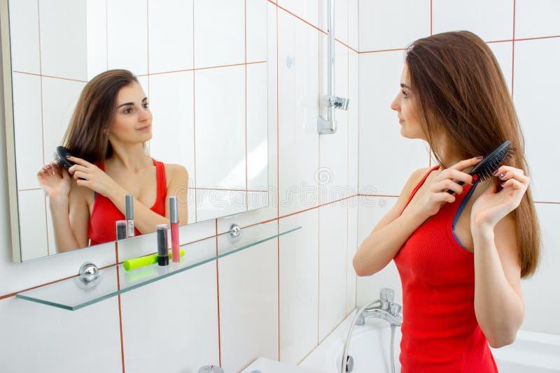 La bella ragazza sta vicino agli specchi e fa l'acconciatura fotografia stock libera da diritti