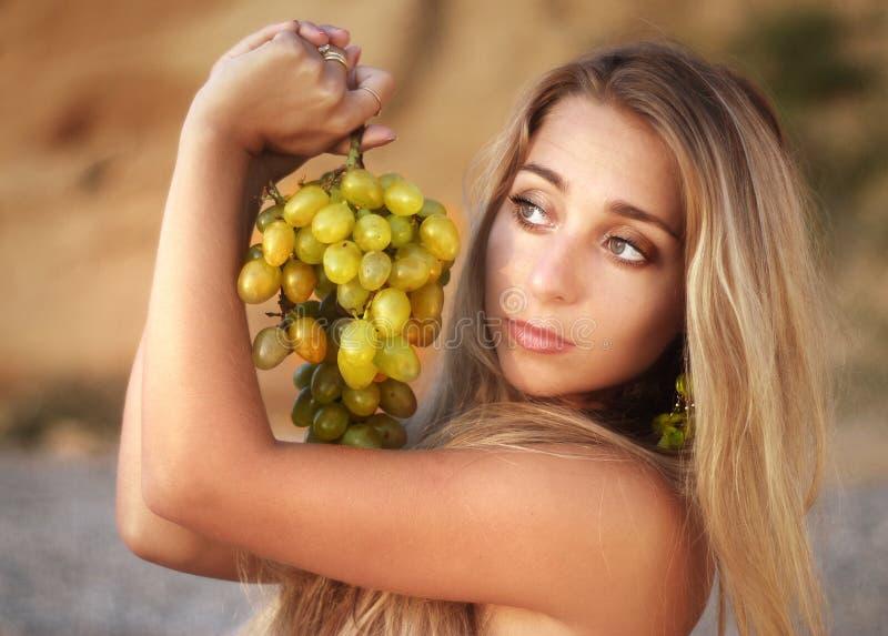 La bella ragazza sulla spiaggia con l'uva fotografia stock