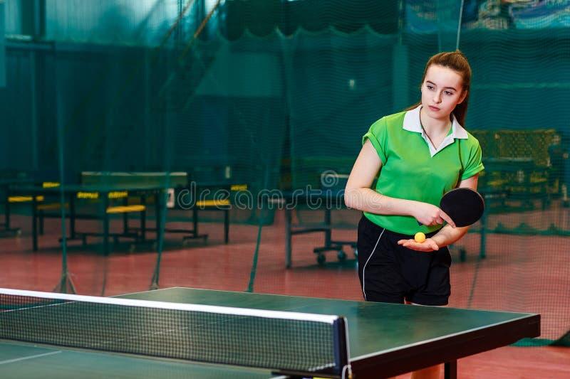 La bella ragazza teenager caucasica di quindici anni in maglietta verde di sport fa un servire nel ping-pong fotografie stock