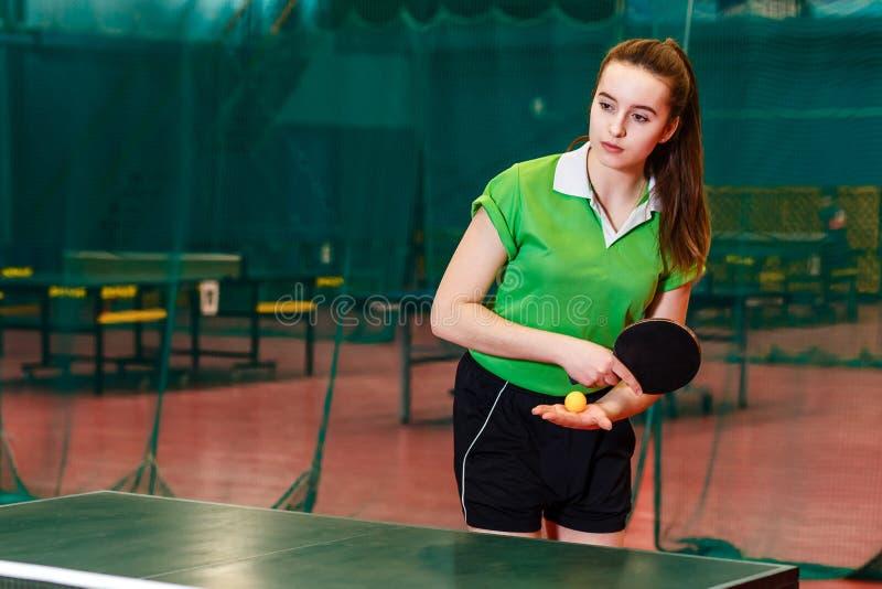 La bella ragazza teenager caucasica di quindici anni in maglietta verde di sport getta la palla nel ping-pong immagini stock libere da diritti