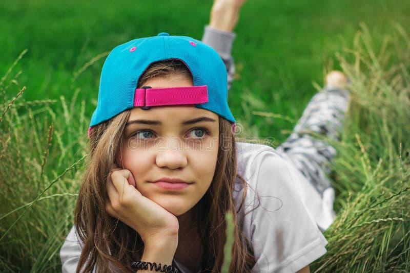 La bella ragazza teenager con i grandi occhi in un berretto da baseball si trova sull'erba e distoglie lo sguardo fotografia stock