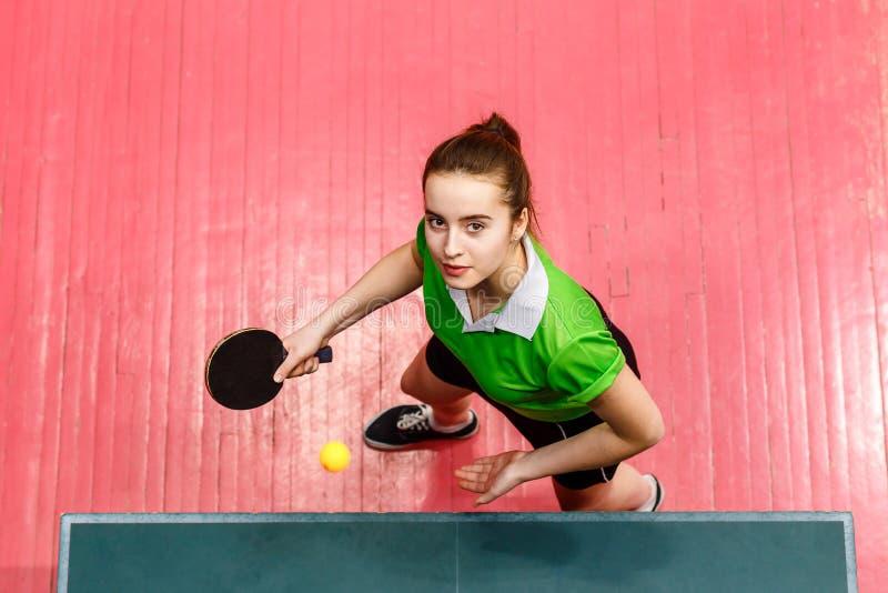 La bella ragazza teenager fa un servire nel ping-pong, vista superiore Anni dell'adolescenza e ping-pong immagini stock libere da diritti