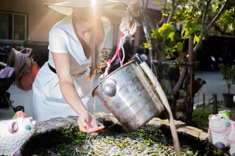 La bella ragazza in un cappello ed in un vestito bianco ricava l'acqua da una luce solare del pozzo di mattina fotografie stock